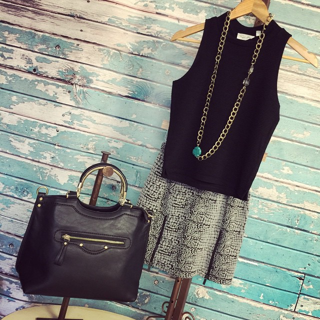 New sleeveless black top paired with a sassy printed skirt and handbag to complete!